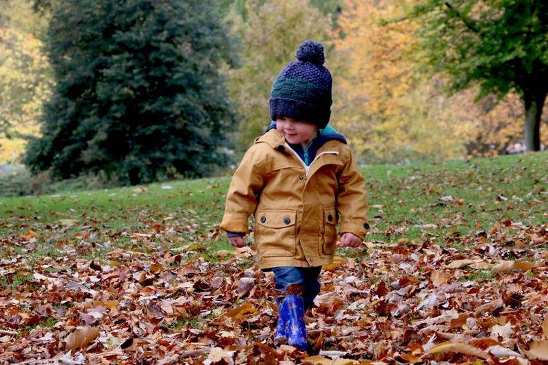 chłopiec ubrany w granatową czapkę z pomponem, kurtkę przeciwdeszczową i kalosze.jpeg