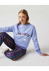 Lacoste - LACOSTE - Fioletowa bluza z logo 3D Unisex Fit. Kolor: różowy, wielokolorowy, fioletowy. Materiał: prążkowany. Wzór: aplikacja