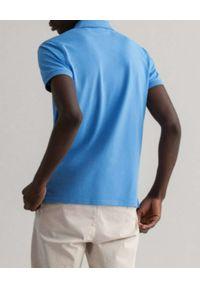 GANT - Niebieski t-shirt polo z kontrastowym logo. Typ kołnierza: polo. Kolor: niebieski. Materiał: materiał. Wzór: haft