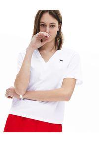 Lacoste - LACOSTE - Biały t-shirt z haftem w serek. Typ kołnierza: dekolt w serek. Kolor: biały. Materiał: jeans, prążkowany, bawełna. Wzór: haft