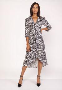 e-margeritka - Elegancka sukienka w panterkę z przedłużanym tyłem - 36. Materiał: materiał, elastan, tkanina, skóra, poliester. Wzór: motyw zwierzęcy. Sezon: jesień, zima. Typ sukienki: asymetryczne, kopertowe. Styl: elegancki. Długość: mini