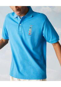 Lacoste - LACOSTE - Niebieska koszulka polo z logo Regular Fit. Typ kołnierza: polo. Kolor: niebieski. Materiał: bawełna. Wzór: haft, prążki, aplikacja. Styl: sportowy, klasyczny