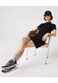 Lacoste - LACOSTE - Czarna sukienka z metalowym logo Slim Fit. Typ kołnierza: polo. Kolor: czarny. Materiał: materiał, prążkowany. Wzór: aplikacja. Styl: klasyczny. Długość: mini