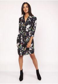 e-margeritka - Sukienka koszulowa wiązana w talii we wzory - 40. Okazja: do pracy, na randkę. Typ kołnierza: kołnierzyk stójkowy. Materiał: tkanina, zamsz, materiał, poliester. Wzór: kwiaty. Sezon: jesień, zima. Typ sukienki: koszulowe. Styl: wizytowy, elegancki