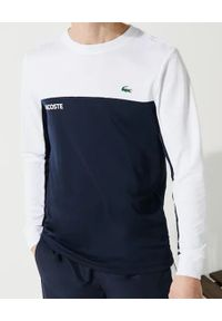 Lacoste - LACOSTE - Sportowy t-shirt z długim rękawem. Kolor: biały. Materiał: tkanina, materiał. Długość rękawa: długi rękaw. Długość: długie. Wzór: napisy. Styl: sportowy
