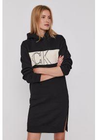 Calvin Klein Jeans - Sukienka. Typ kołnierza: kaptur. Kolor: czarny. Materiał: dzianina, bawełna. Długość rękawa: długi rękaw. Wzór: aplikacja
