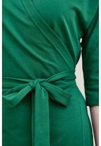 Marie Zélie - Sukienka Filomena ciemnozielona. Typ kołnierza: dekolt kopertowy. Kolekcja: moda ciążowa. Kolor: zielony. Materiał: materiał, bawełna, dzianina, skóra, tkanina, elastan. Typ sukienki: proste, kopertowe. Styl: młodzieżowy, klasyczny