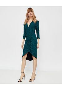 THECADESS - Błyszcząca zielona sukienka Alicante. Kolor: zielony. Materiał: materiał. Typ sukienki: kopertowe, wyszczuplające. Długość: midi