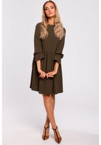 e-margeritka - Sukienka rozkloszowana odcięta w pasie khaki - xl. Okazja: do pracy. Kolor: brązowy. Materiał: tkanina, poliester, materiał, elastan. Sezon: jesień. Typ sukienki: proste, rozkloszowane. Styl: elegancki. Długość: midi