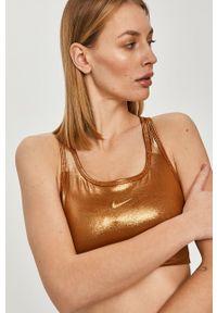 Nike - Biustonosz sportowy. Kolor: złoty. Materiał: włókno, skóra, tkanina. Technologia: Dri-Fit (Nike)
