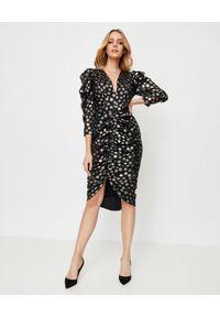 THECADESS - Modelująca sukienka w złote kropki Alicante. Kolor: czarny. Materiał: tkanina. Wzór: kropki. Typ sukienki: kopertowe, wyszczuplające. Długość: midi