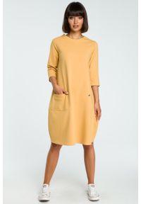 e-margeritka - Luźna dzianinowa sukienka za kolano do pracy - 42, żółty. Okazja: do pracy. Typ kołnierza: kołnierzyk stójkowy. Kolor: czarny, szary, żółty. Materiał: dzianina. Wzór: aplikacja. Sezon: jesień, zima. Typ sukienki: bombki