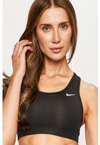 Nike - Biustonosz sportowy. Kolor: czarny. Materiał: włókno, skóra, tkanina. Rodzaj stanika: odpinane ramiączka. Technologia: Dri-Fit (Nike)