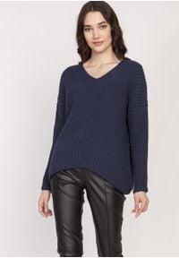 e-margeritka - Sweter oversize granatowy - s/m. Typ kołnierza: dekolt w serek. Kolor: niebieski. Materiał: akryl, wełna, dzianina. Długość rękawa: raglanowy rękaw. Wzór: ze splotem