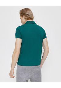 MONCLER - Zielona koszulka polo. Okazja: na co dzień. Typ kołnierza: polo. Kolor: zielony. Materiał: bawełna. Wzór: aplikacja. Styl: sportowy, klasyczny, casual