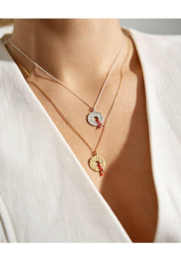MOKOBELLE - Pozłacany łańcuszek z rozetką Mokobelle i czerwoną nitką. Materiał: pozłacane. Kolor: złoty. Wzór: aplikacja