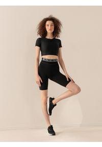 4f - Spodenki treningowe damskie Anna Lewandowska x 4F. Stan: podwyższony. Kolor: czarny. Materiał: materiał. Wzór: nadruk, gładki. Sport: fitness