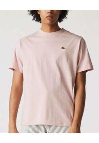 Lacoste - LACOSTE - Jasnoróżowy t-shirt z metalowym logo Regular Fit. Kolor: różowy, wielokolorowy, fioletowy. Materiał: bawełna. Wzór: aplikacja. Styl: sportowy