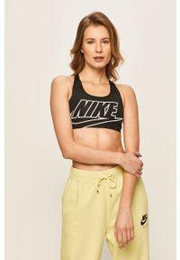 Nike - Biustonosz sportowy. Kolor: czarny. Materiał: włókno, skóra, tkanina. Technologia: Dri-Fit (Nike). Wzór: nadruk