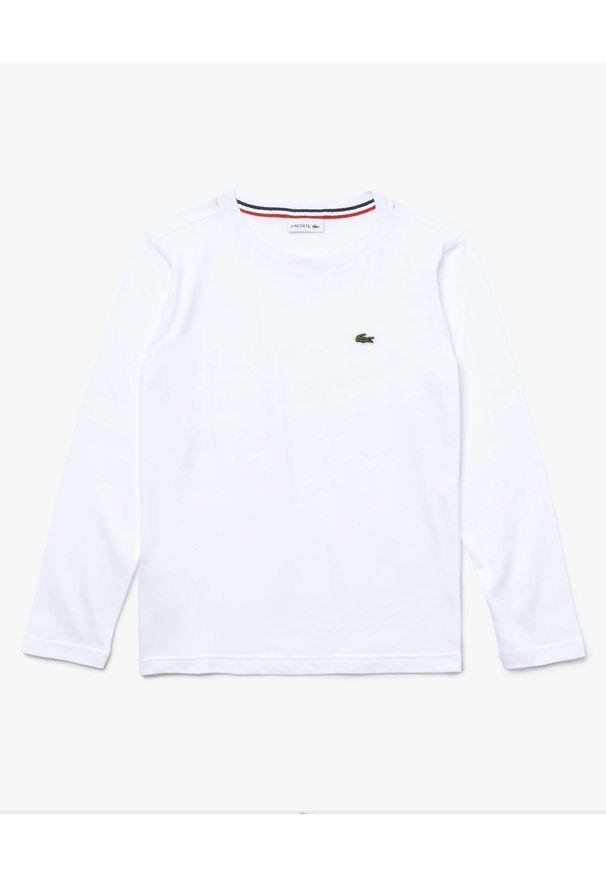 Lacoste - LACOSTE - Biała koszulka z długim rękawem. Kolor: biały. Materiał: bawełna, prążkowany. Długość rękawa: długi rękaw. Długość: długie. Wzór: aplikacja