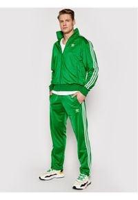 Adidas - adidas Spodnie dresowe Firebird Tp GN3520 Zielony Regular Fit. Kolor: zielony. Materiał: dresówka