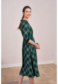 Marie Zélie - Sukienka Greta krata zielona z fioletem. Typ kołnierza: dekolt kopertowy. Kolor: zielony. Materiał: bawełna, wiskoza, dzianina, materiał, tkanina, skóra, poliester. Długość rękawa: krótki rękaw. Typ sukienki: kopertowe. Styl: klasyczny. Długość: midi