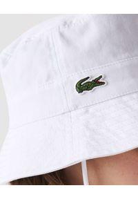 Lacoste - LACOSTE - Biały kapelusz typu bucket ze ściągaczem. Kolor: biały. Materiał: bawełna. Wzór: haft