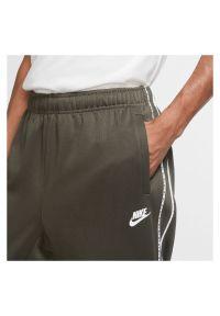 Spodnie treningowe męskie Nike Sportswear Jogger CZ7823. Kolor: brązowy. Materiał: dzianina, materiał, poliester. Wzór: napisy, ze splotem. Sport: fitness, turystyka piesza