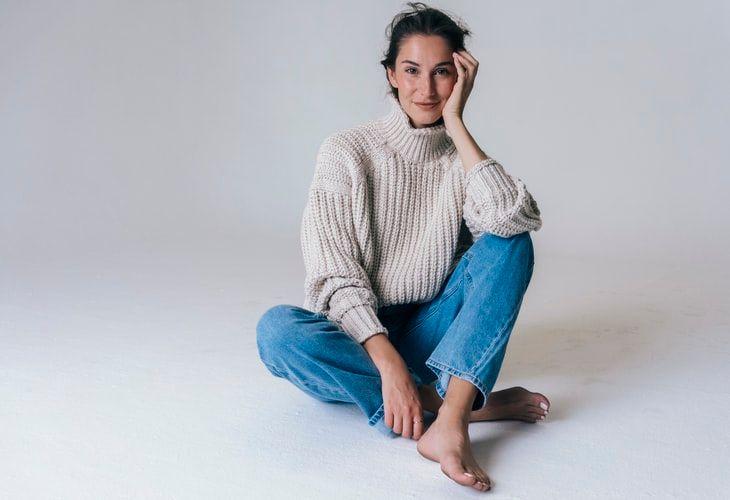 kobieta ubrana w sweter w kremowym kolorze i jeansy.jpeg