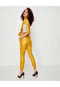 JOANNA MUZYK - Żółta bluzka ortalionowa. Kolor: żółty. Materiał: tkanina. Styl: sportowy