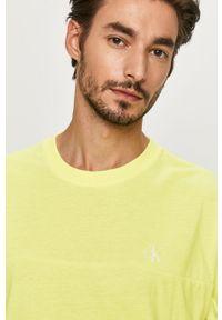 Żółty t-shirt Calvin Klein Jeans casualowy, z aplikacjami, na co dzień