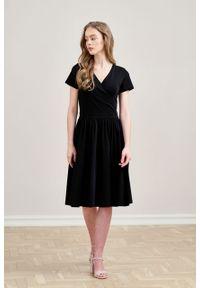 Marie Zélie - Sukienka Larissa czarna krótki rękaw. Typ kołnierza: dekolt kopertowy. Kolor: czarny. Materiał: bawełna, dzianina, materiał, elastan, skóra. Długość rękawa: krótki rękaw. Typ sukienki: kopertowe