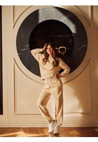 4f - Spodnie dresowe z szerokimi nogawkami damskie Anna Lewandowska x 4F. Kolor: beżowy. Materiał: dresówka. Wzór: nadruk