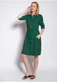 e-margeritka - Sukienka koszulowa na guziki wiązana w talii zielona - 42. Okazja: na co dzień. Kolor: zielony. Materiał: tkanina, wiskoza, materiał. Długość rękawa: długi rękaw. Typ sukienki: koszulowe. Styl: casual. Długość: midi