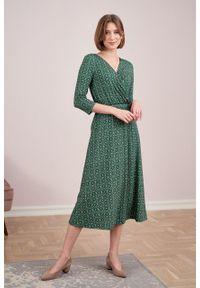 Marie Zélie - Sukienka Rita Beatica zielona. Typ kołnierza: dekolt kopertowy. Kolor: zielony. Materiał: wiskoza, dzianina, materiał, elastan, tkanina. Długość rękawa: krótki rękaw. Wzór: kwiaty. Sezon: jesień. Typ sukienki: proste, kopertowe