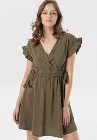 Born2be - Ciemnozielona Sukienka Corraenelle. Typ kołnierza: kołnierz z falbankami. Kolor: zielony. Długość rękawa: krótki rękaw. Typ sukienki: kopertowe. Długość: mini