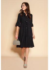 e-margeritka - Sukienka koszulowa z falbanami do kolan czarna - 42/44. Typ kołnierza: kołnierzyk stójkowy. Kolor: czarny. Materiał: tkanina, poliester, materiał. Typ sukienki: koszulowe. Styl: elegancki. Długość: midi