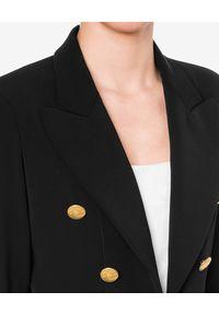 MOSCHINO - Czarna sukienka z logowanymi guzikami. Kolor: czarny. Materiał: materiał. Długość rękawa: długi rękaw. Typ sukienki: kopertowe. Styl: elegancki. Długość: mini