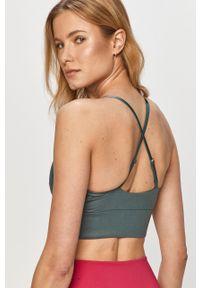 Nike - Biustonosz sportowy. Kolor: zielony. Rodzaj stanika: odpinane ramiączka, wyciągane miseczki