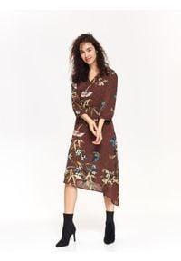 TOP SECRET - Elegancka sukienka kopertowa w druk. Okazja: na co dzień. Kolor: brązowy. Materiał: tkanina. Długość rękawa: krótki rękaw. Wzór: kwiaty. Sezon: jesień, zima. Typ sukienki: kopertowe. Styl: elegancki