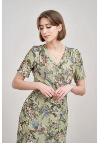 Marie Zélie - Sukienka Irmina Phoenix zielona. Kolor: zielony. Materiał: wiskoza, materiał, tkanina, skóra, poliester. Długość rękawa: krótki rękaw. Wzór: napisy. Typ sukienki: proste, kopertowe