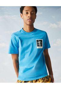 Lacoste - LACOSTE - Niebieski t-shirt z termoczułym nadrukiem Regular fit. Kolor: niebieski. Materiał: bawełna, jersey, jeans, prążkowany. Wzór: nadruk