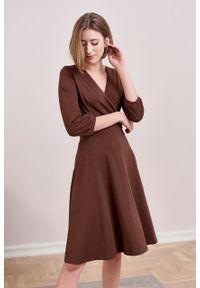 Marie Zélie - Sukienka Hermia czekoladowa. Typ kołnierza: dekolt kopertowy. Kolor: brązowy. Materiał: bawełna, dzianina, materiał, elastan, skóra. Długość rękawa: krótki rękaw. Typ sukienki: kopertowe