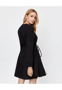 VALENTINO - Czarna sukienka mini z wiązaniem. Okazja: do pracy. Kolor: czarny. Materiał: tkanina, jedwab, wełna. Długość rękawa: długi rękaw. Typ sukienki: rozkloszowane. Styl: elegancki. Długość: mini