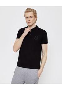 MONCLER - Czarna koszulka polo. Okazja: na co dzień. Typ kołnierza: polo. Kolor: czarny. Materiał: dresówka, jeans, bawełna. Wzór: aplikacja. Styl: klasyczny, casual