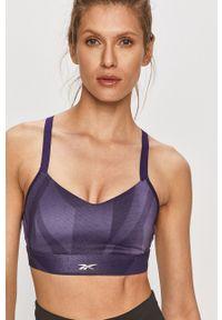 Reebok - Biustonosz sportowy. Kolor: fioletowy. Materiał: skóra. Rodzaj stanika: odpinane ramiączka