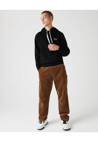 Lacoste - LACOSTE - Czarna bluza z kapturem. Okazja: na co dzień. Typ kołnierza: kaptur. Kolor: czarny. Materiał: bawełna, jeans, prążkowany. Wzór: aplikacja. Styl: sportowy, casual