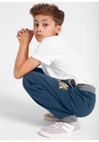 Spodnie dresowe chłopięce bonprix ciemnoniebieski. Kolor: niebieski. Materiał: dresówka. Wzór: napisy, nadruk, aplikacja. Styl: sportowy
