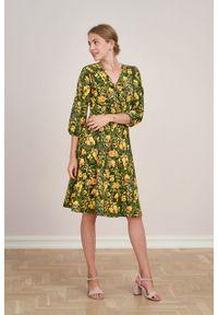 Marie Zélie - Sukienka Hermia Prado ciemnozielona. Typ kołnierza: dekolt kopertowy. Kolor: zielony. Materiał: bawełna, dzianina, materiał, elastan, skóra. Długość rękawa: krótki rękaw. Typ sukienki: kopertowe