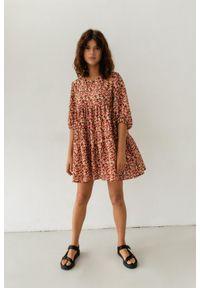 Marsala - Sukienka oversize z przeszyciami z printem w odcieniu czerwono-pomarańczowym - BLUSH BY MARSALA. Kolekcja: moda ciążowa. Kolor: pomarańczowy, czerwony, wielokolorowy. Materiał: wiskoza, materiał. Długość rękawa: krótki rękaw. Wzór: nadruk. Typ sukienki: oversize